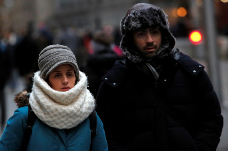 People walk along Wall Street ahead of a cold weather system across the region in Manhattan, New York City, U.S.,