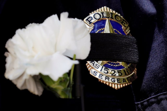 A Dallas police sergeant wears a mourning band and flower on his badge during a prayer vigil, one day after a lone gunman ambushed and killed five police officers at a protest decrying police shootings of black men, in Dallas, Texas, U.S.,