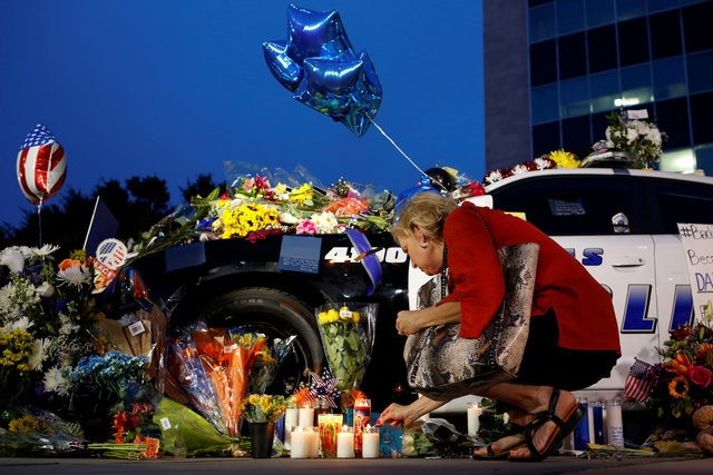 A woman lights a candle at a makeshift memorial at Dallas Police Headquarters,
