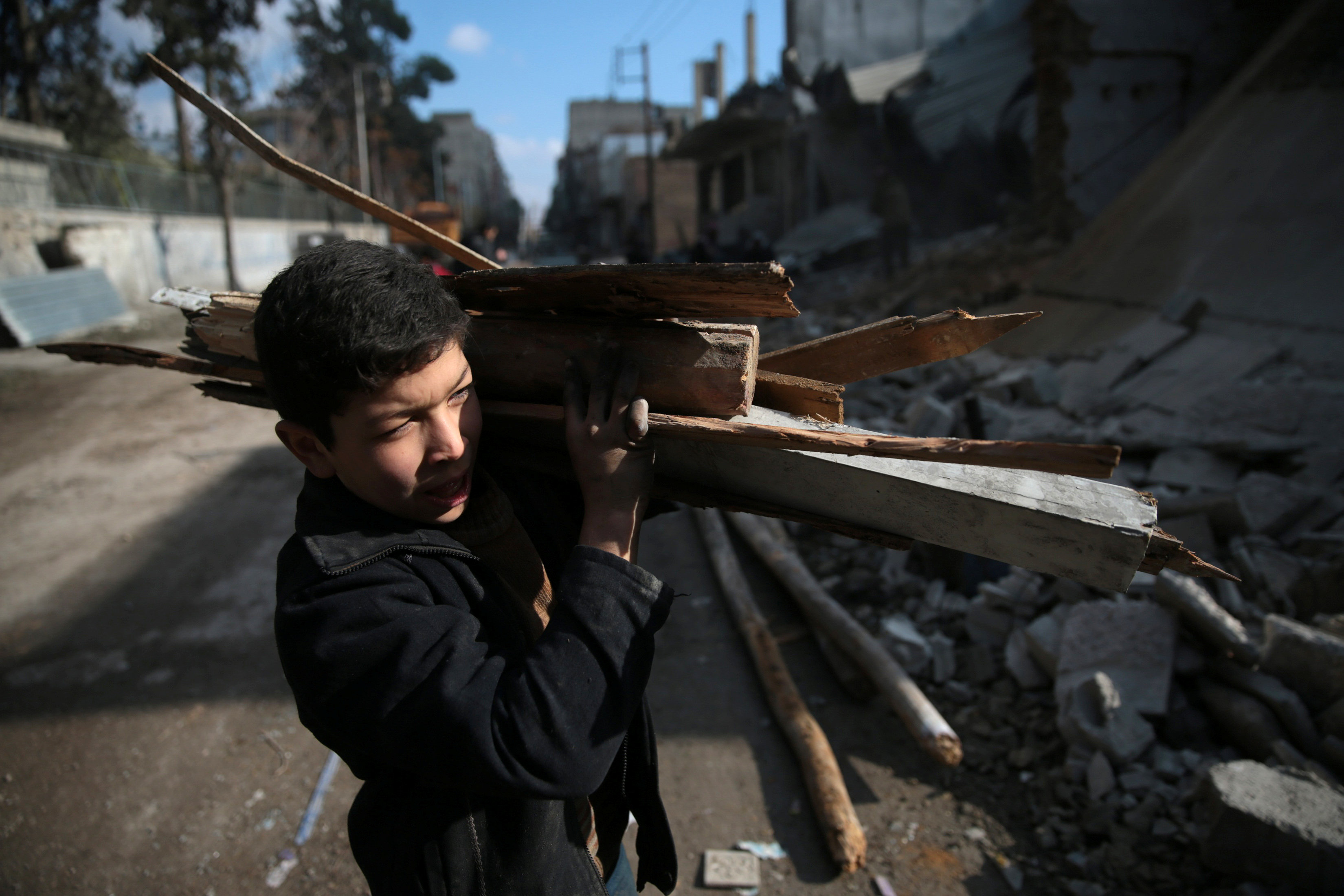 A boy collects firewood in the rebel held besieged city of Douma, in the eastern Damascus