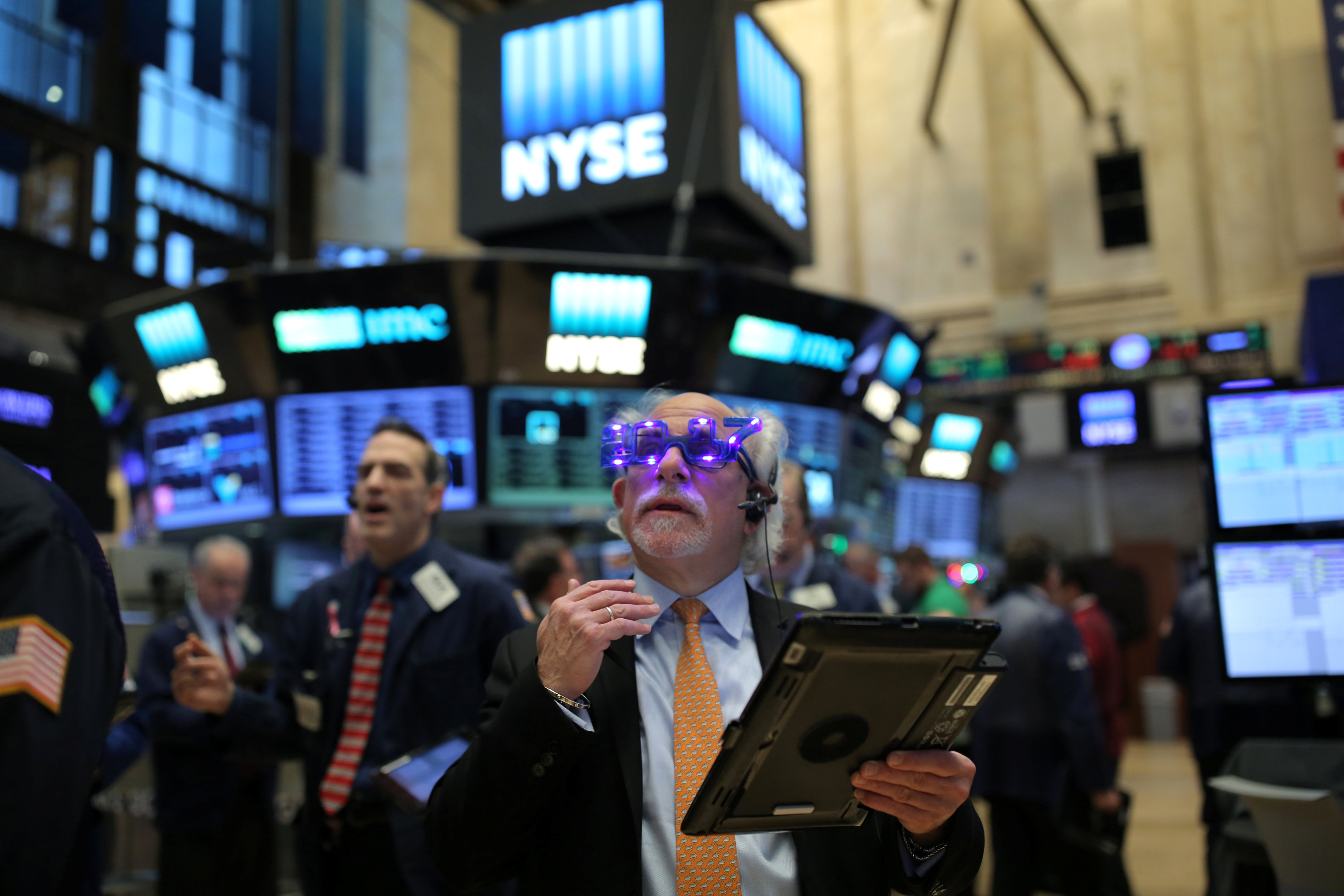 "A trader wears glasses that say ""2017"" ahead of the new year on the floor of the New York Stock Exchange (NYSE) in Manhattan, New York City, U.S., December 30, 2016."