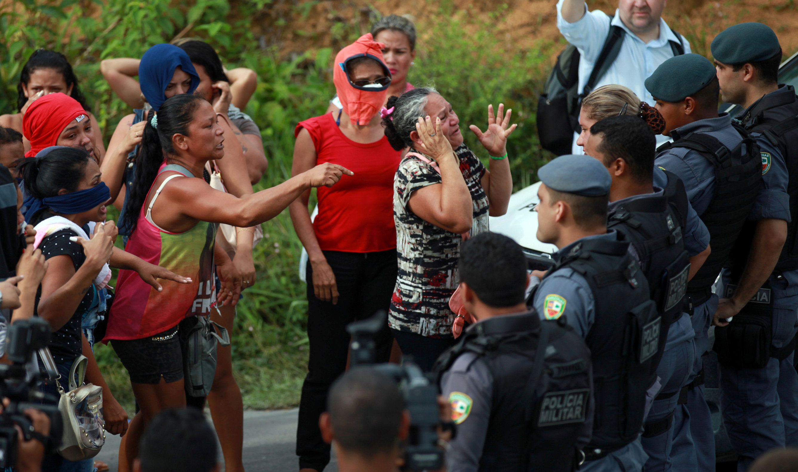 Relatives of prisoners react near riot police at a checkpoint close to the prison where around 60 people were killed in a prison riot in the Amazon jungle city of Manaus, Brazil