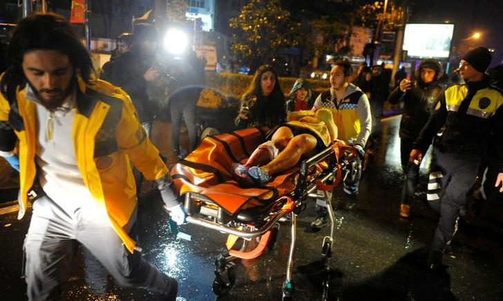 An injured woman is carried to an ambulance from a nightclub where a gun attack took place during a New Year party in Istanbul, Turkey.