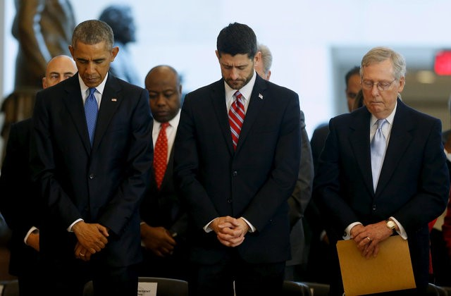 U.S. President Barack Obama (L-R), House Speaker Paul Ryan (R-WI) and Senate Majority Leader Mitch McConnell (R-KY) bow their heads in prayer at the end of a ceremony commemorating the 150th anniversary of the 13th Amendment, which formally abolished slavery in the aftermath of the U.S. Civil War, at the U.S. Capitol in Washington
