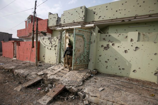 A member of Iraqi security forces inspects a house in the Intisar district of eastern Mosul, Iraq,