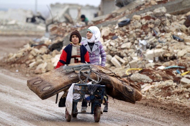 Samah, 11, and her brother, Ibrahim, transport their salvaged belongings from their damaged house in Doudyan village in northern Aleppo