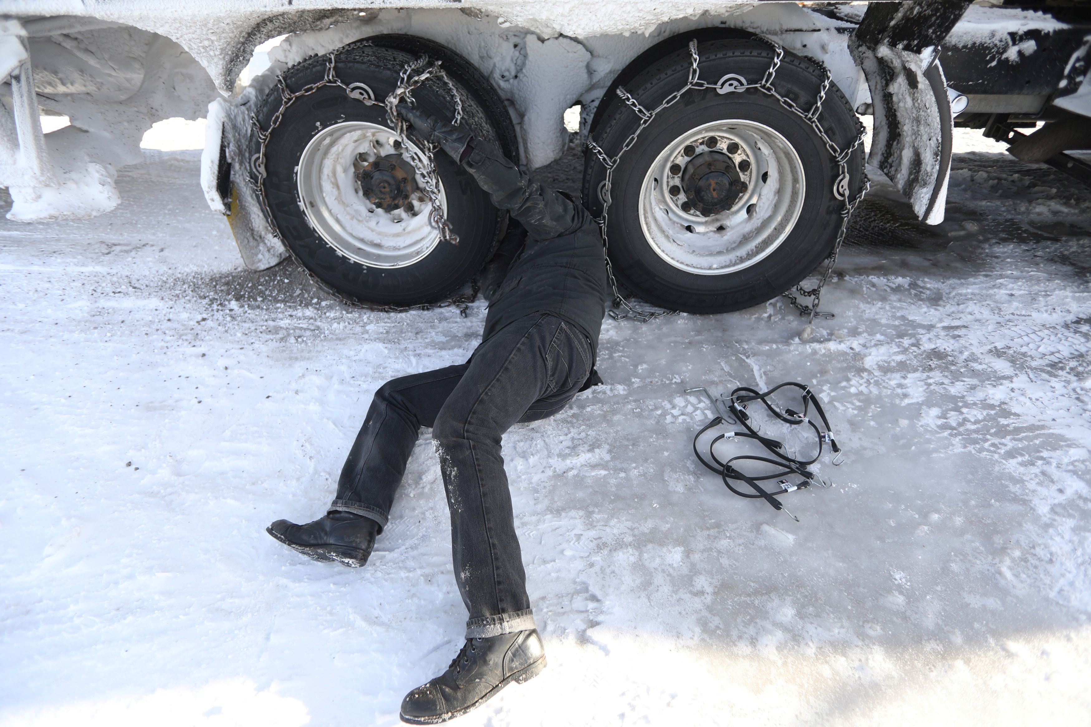 Semi truck driver removes chains from truck