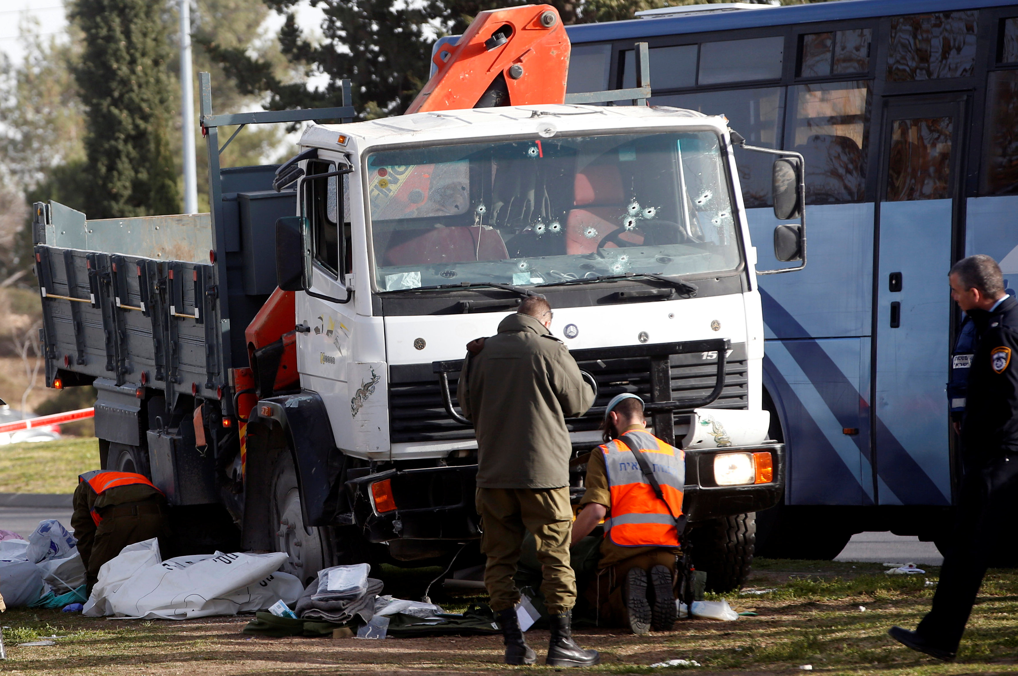 Israeli soldiers work at the scene where police said a Palestinian rammed his truck into a group of Israeli soldiers on a popular promenade in Jerusalem