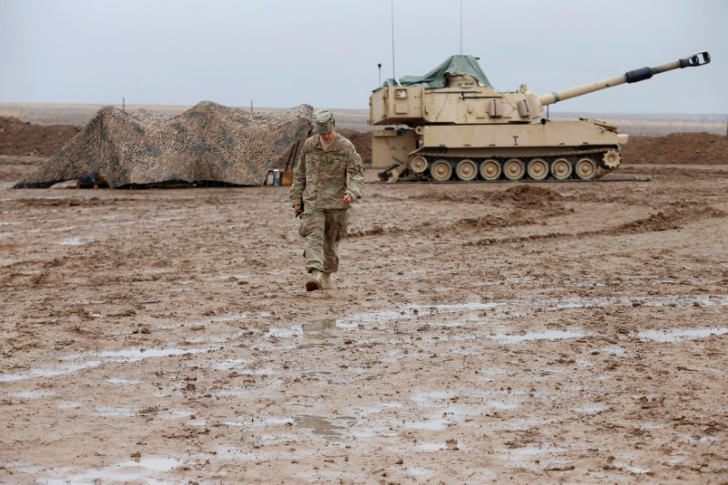 US Soldier walks in front of tank in Iraq