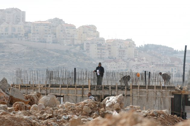 Palestinian laborers working at construction site on Israeli settlement
