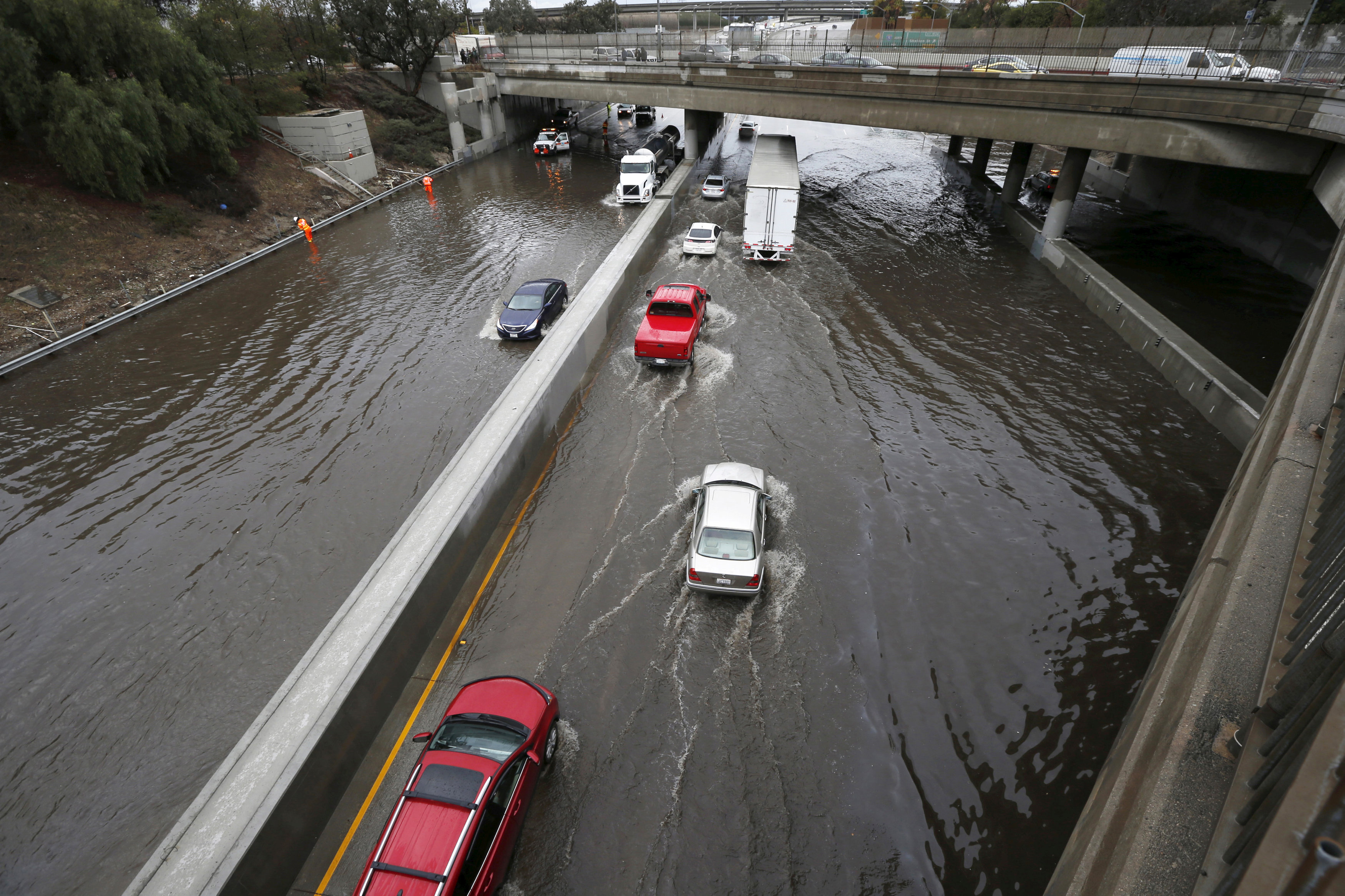 Vehicles drive on flooded freeway