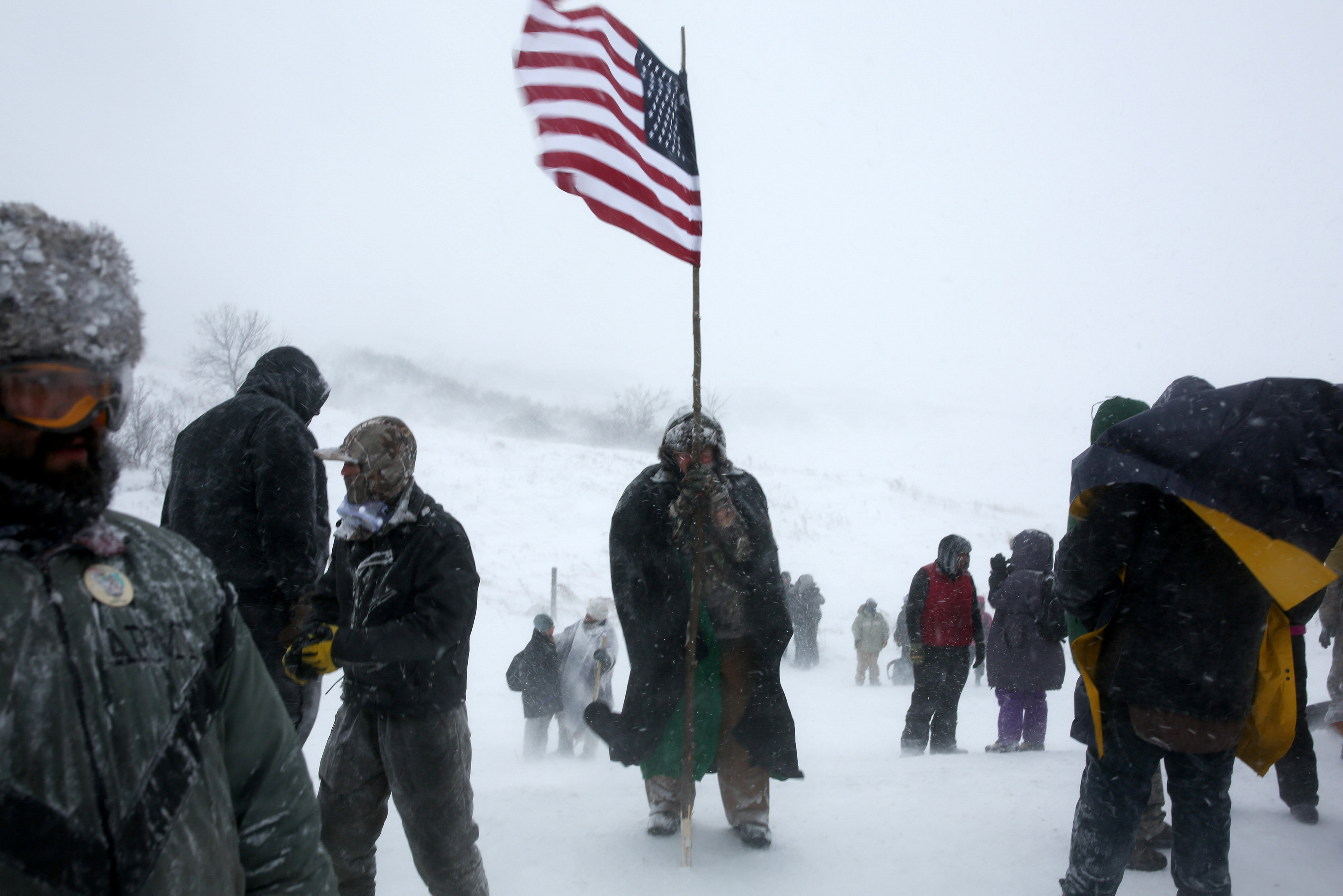 man holds American flag at Dakota Access Pipeline protest