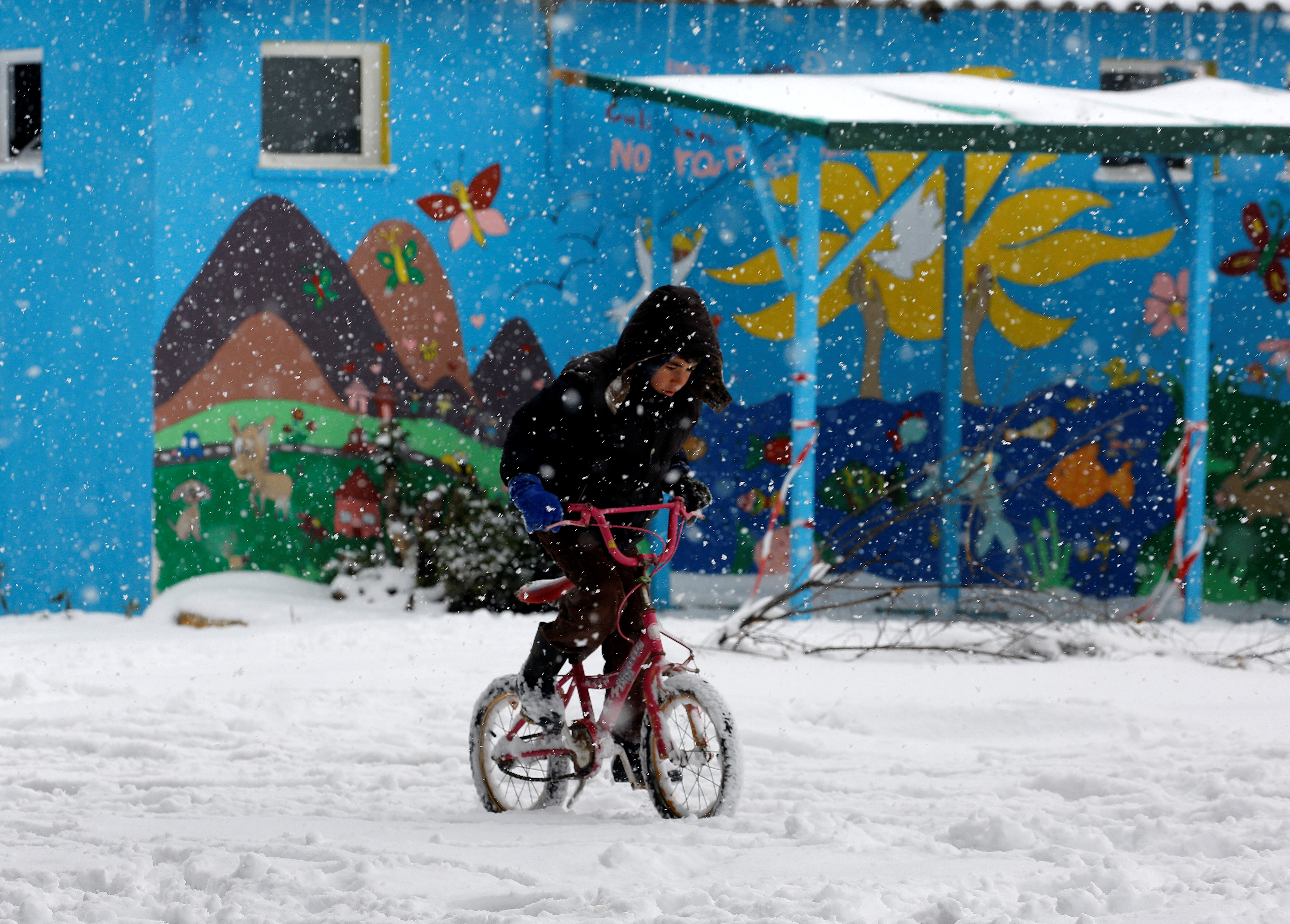refugee boy rides bike through snow