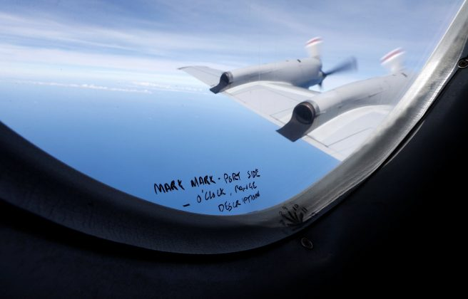 Handwritten notes on how a crew member should report the sighting of debris in the southern Indian Ocean is pictured on a window aboard a Royal New Zealand Air Force P-3K2 Orion aircraft searching for missing Malaysian Airlines flight MH370