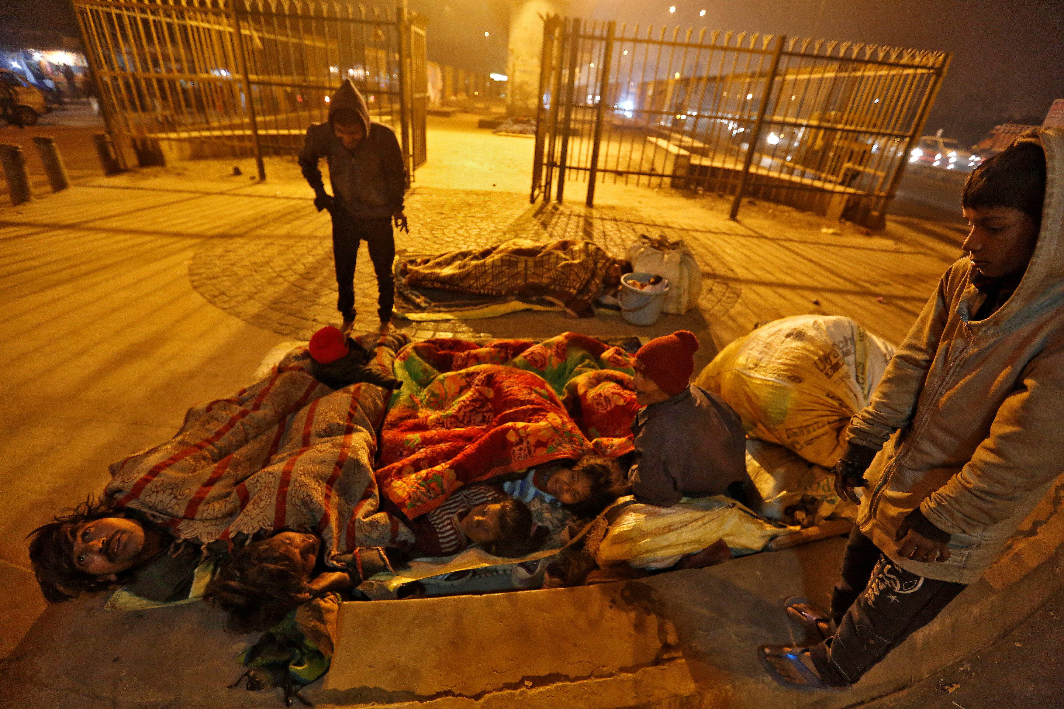 A family gather under blankets to shelter from the cold beneath a flyover in Delhi, India