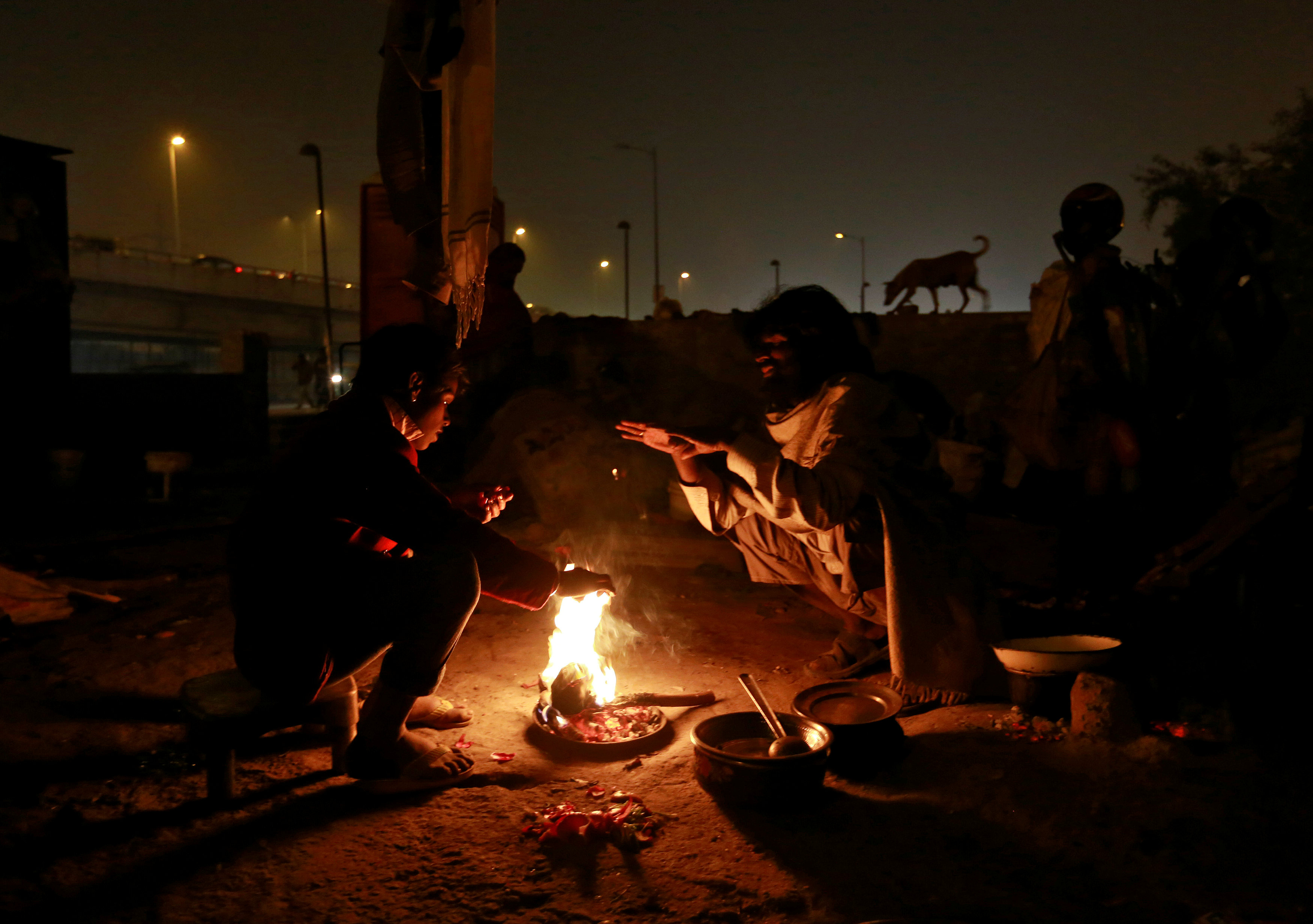 People warm themselves by a fire to escape the cold in Delhi, India