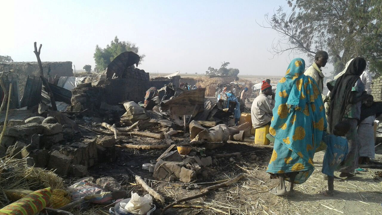 People walk at the site after a bombing attack of an internally displaced persons camp in Rann, Nigeria