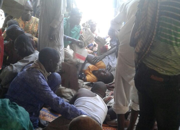 Injured people are comforted at the site after a bombing attack of an internally displaced persons camp in Rann, Nigeria