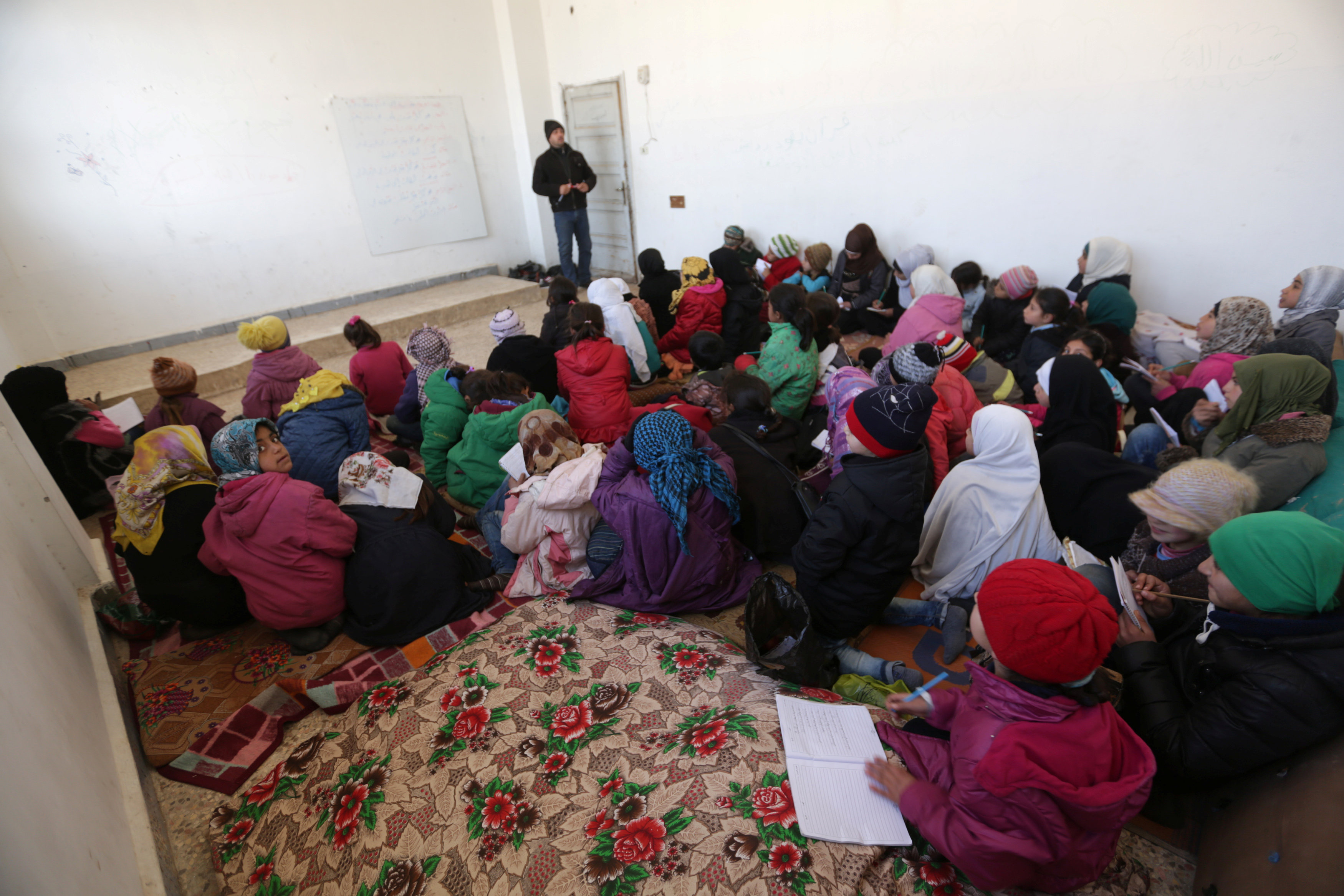 schoolchildren sit on mats as they return to school in Aleppo after Islamic State driven out