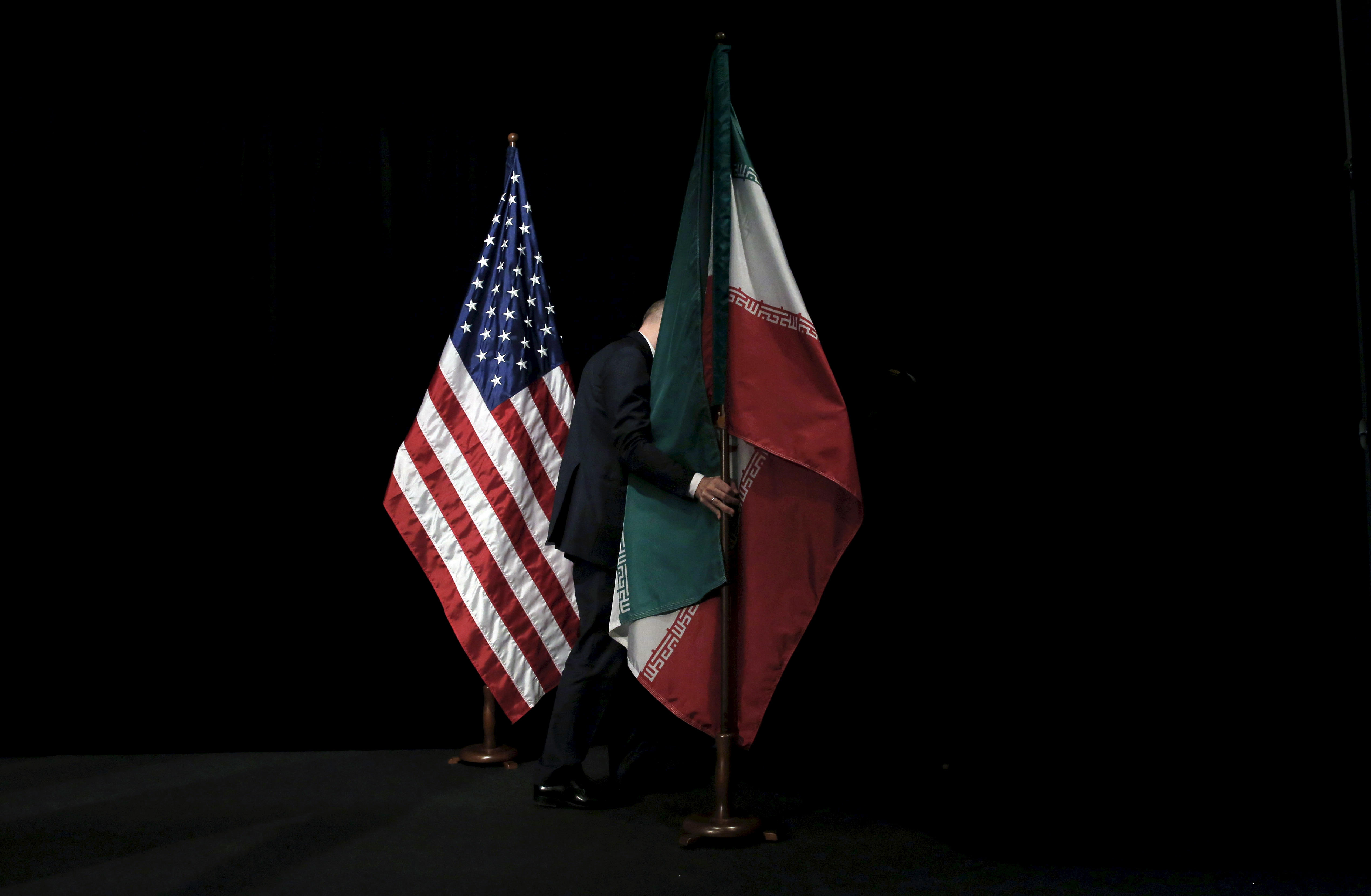 A staff member removes the Iranian flag from the stage after a group picture with foreign ministers and representatives of Unites States, Iran, China, Russia, Britain, Germany, France and the European Union during the Iran nuclear talks at the Vienna International Center in Vienna, Austria