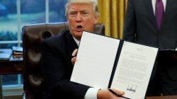 President Donald Trump holds up executive order