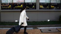 woman walks past electronic board with stock market numbers on it
