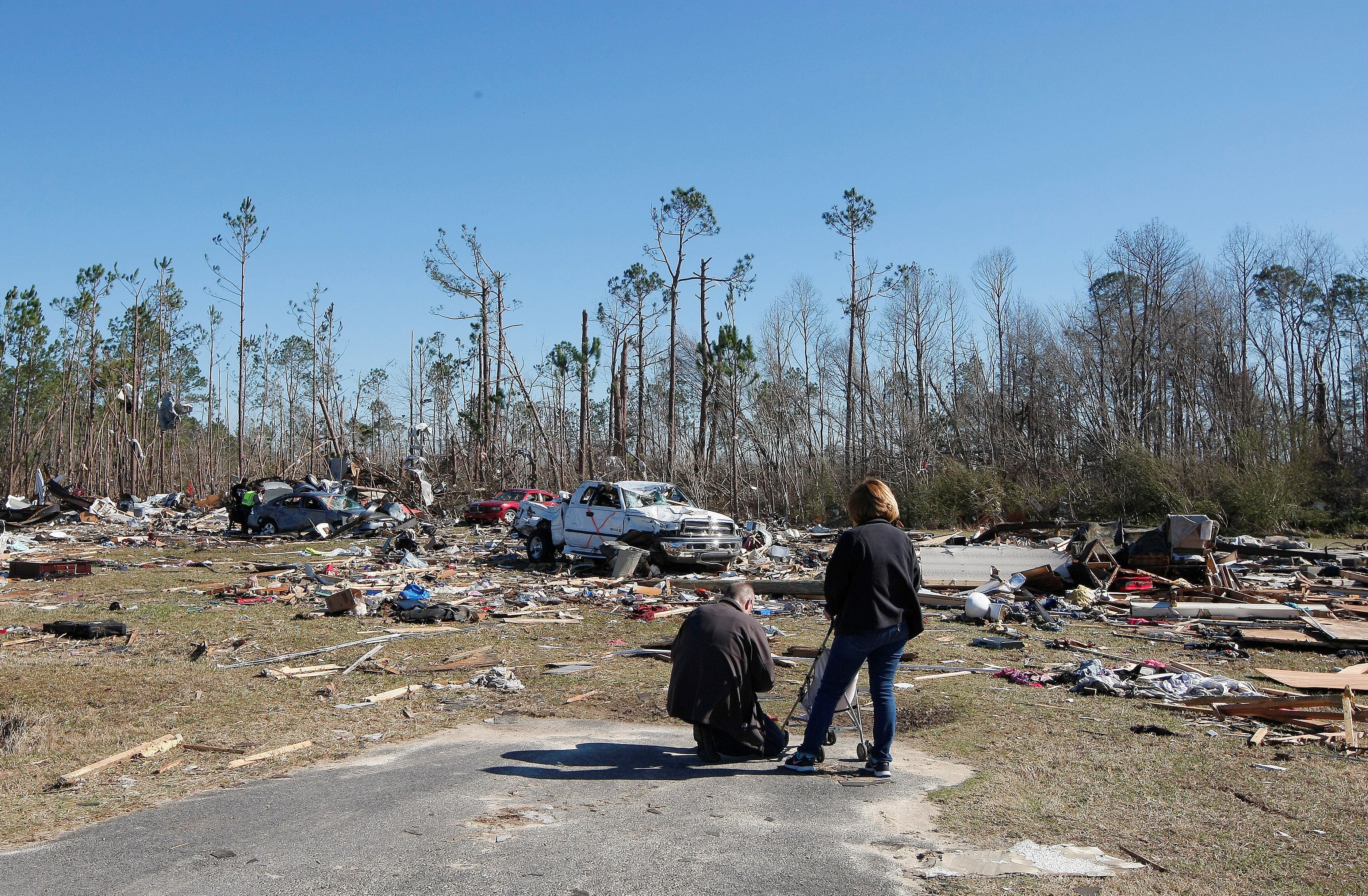 relief workers look at area that was struck by tornado