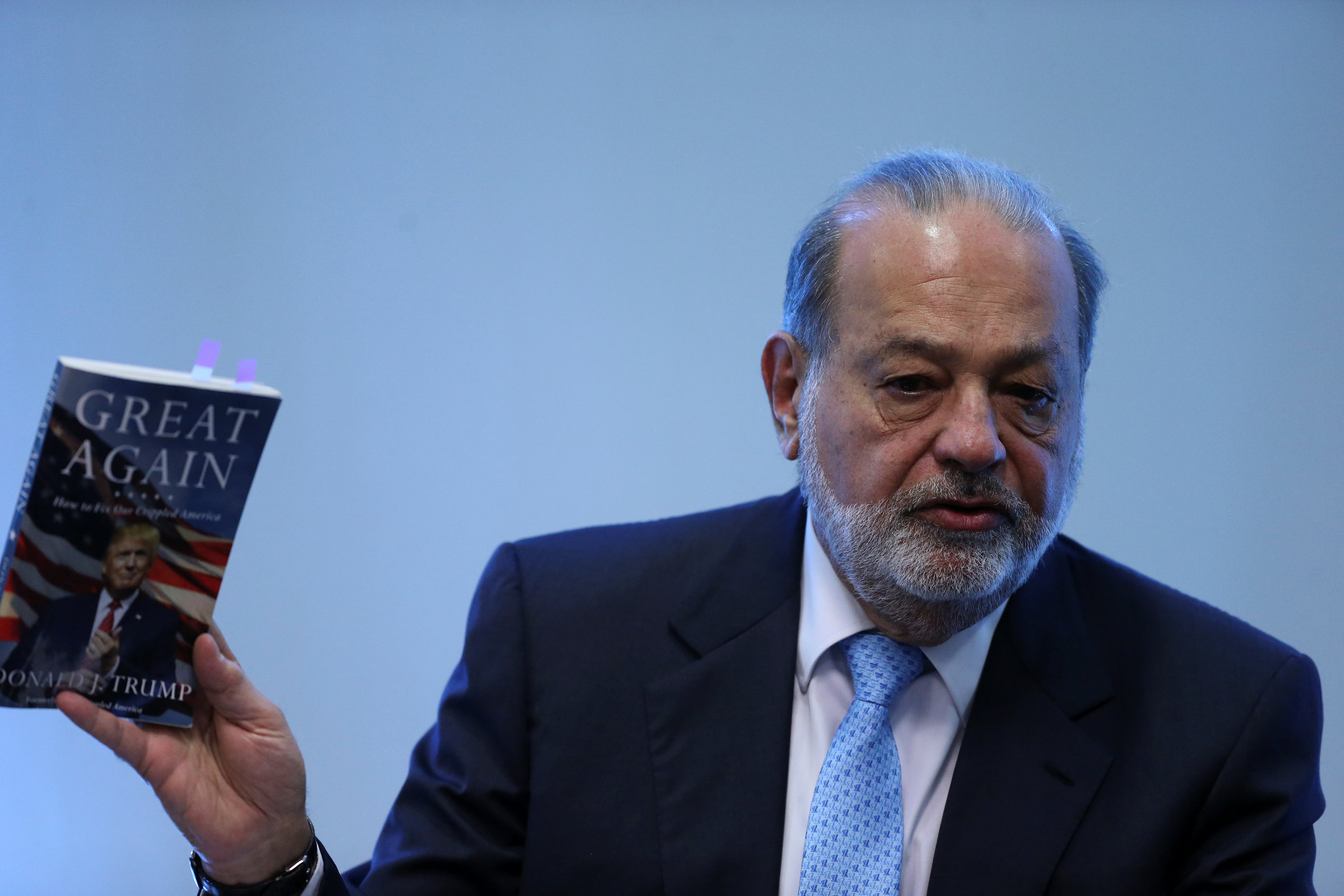 """Mexican billionaire Carlos Slim shows the book """"Crippled America: How to make America great again"""" by Donald Trump during a news conference in Mexico City, Mexico"""