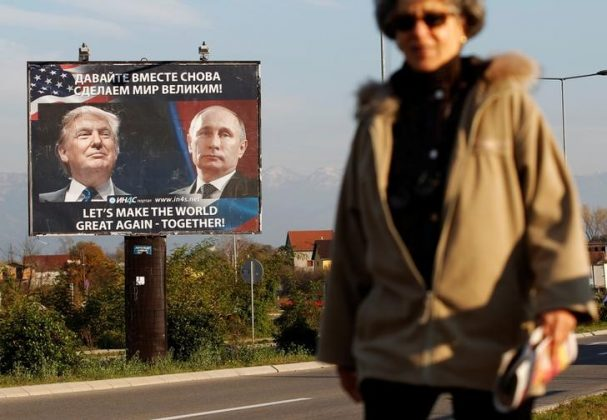 woman passes billboard of Trump and Putin together