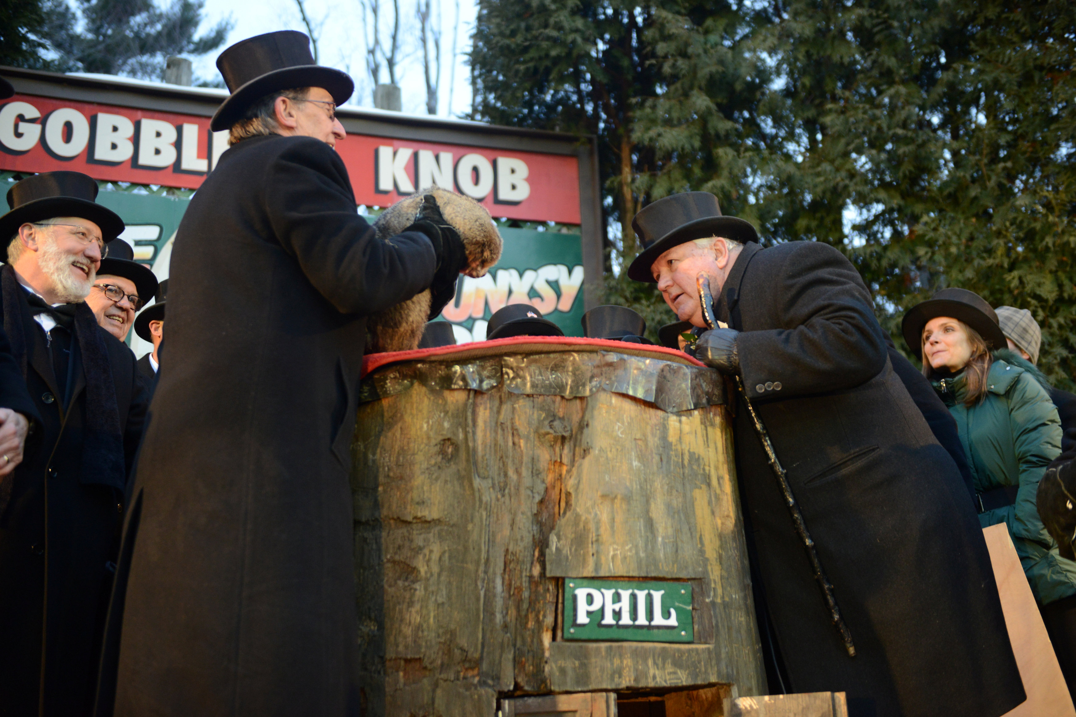 Groundhog Club President Bill Deeley listens to Punxsutawney Phil for his forecast while handler Ron Ploucha holds him at Gobbler's Knob on the 131st Groundhog Day in Punxsutawney, Pennsylvania, U.S. February 2, 2017.