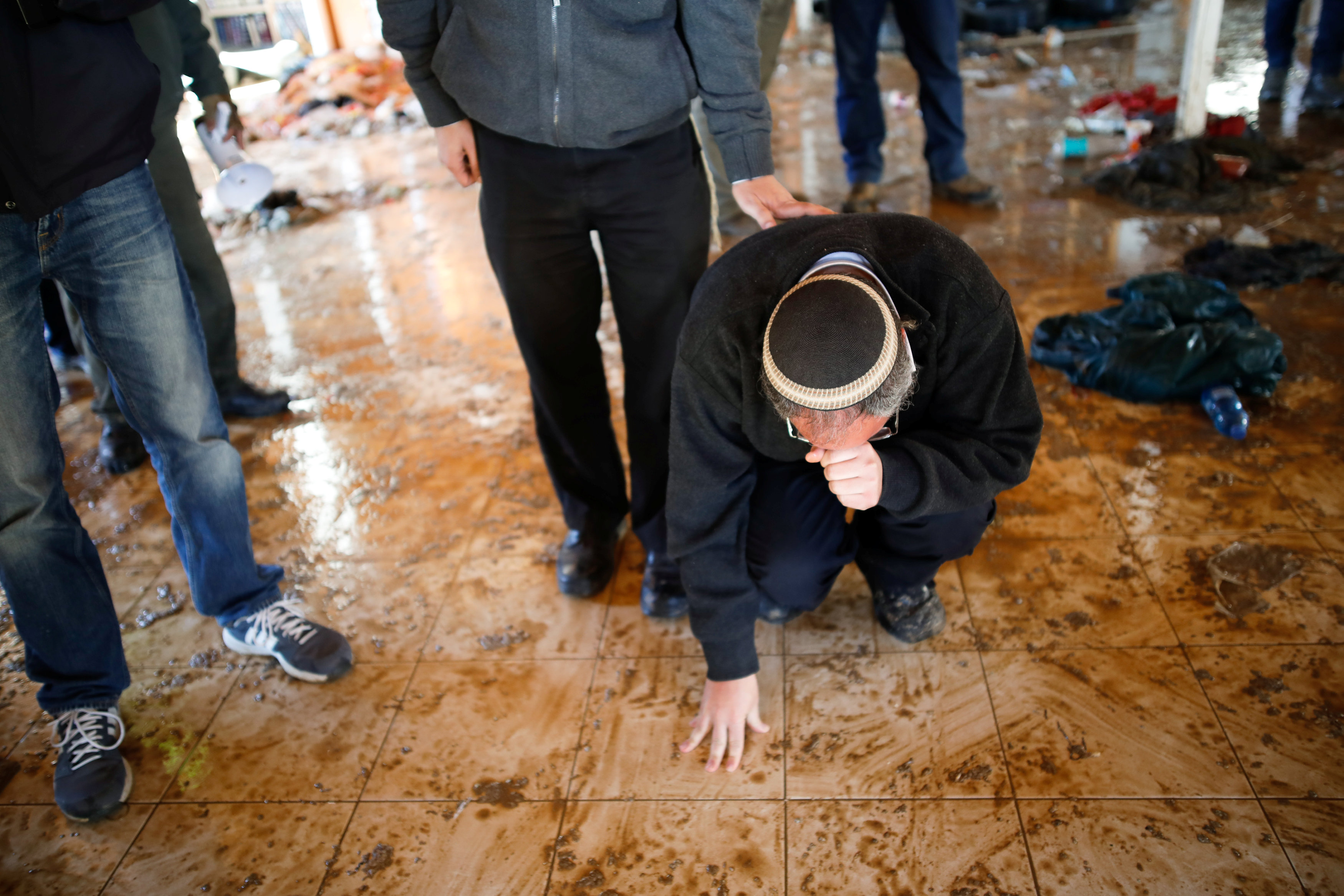 An Israeli settler touches the floor of a synagogue after it was evacuated during the second day of an operation by Israeli forces to evict the illegal outpost of Amona in the occupied West Bank
