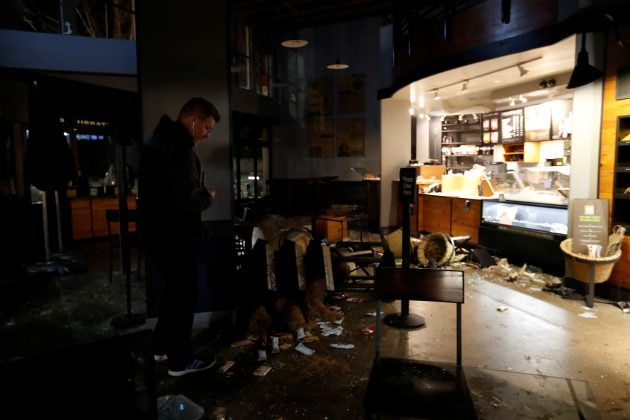 A worker surveys the damage to a vandalized Starbucks after a student protest turned violent at UC Berkeley during a demonstration over right-wing speaker Milo Yiannopoulos, who was forced to cancel his talk, in Berkeley, California.