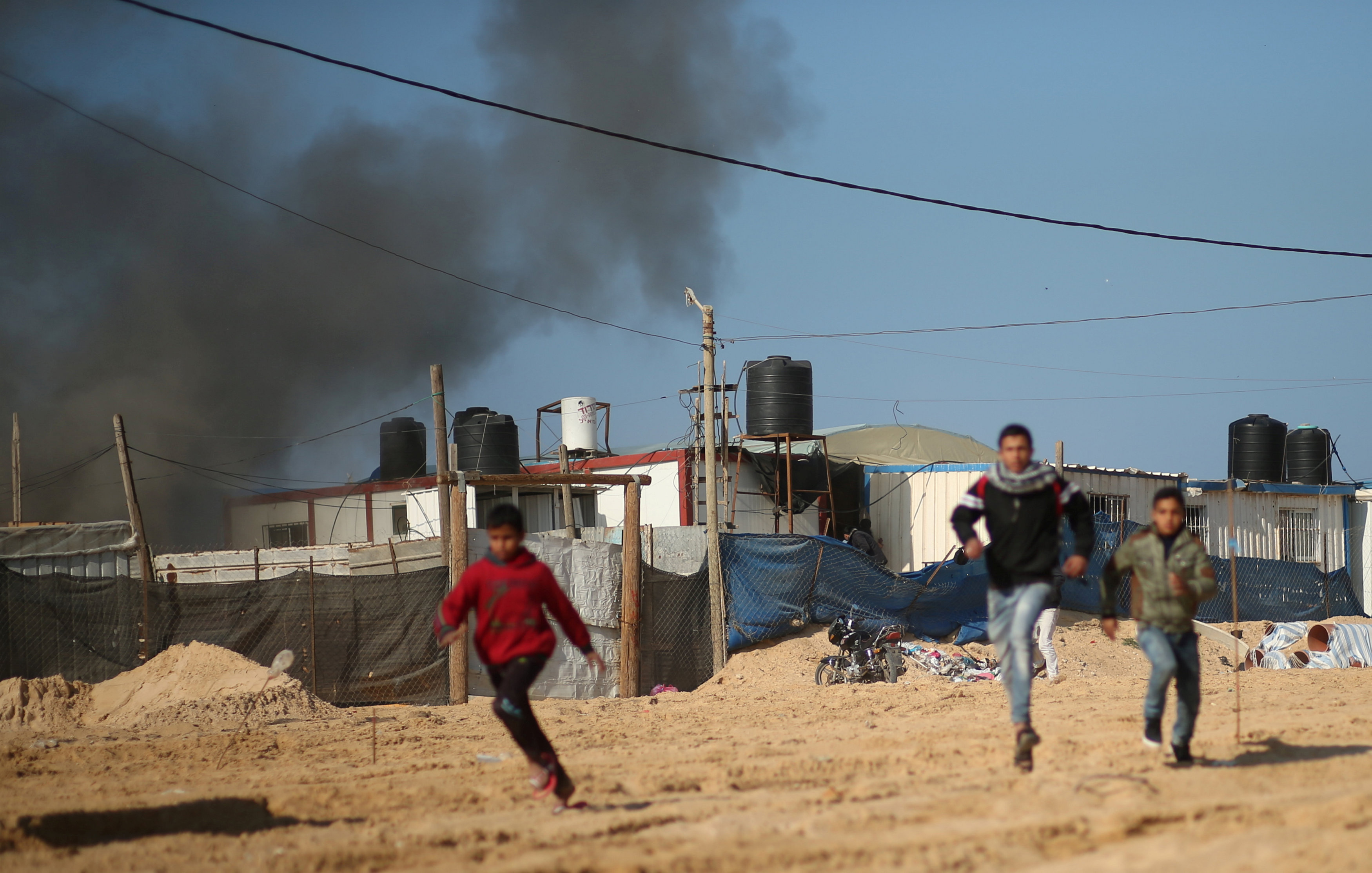 Palestinians run from air strike