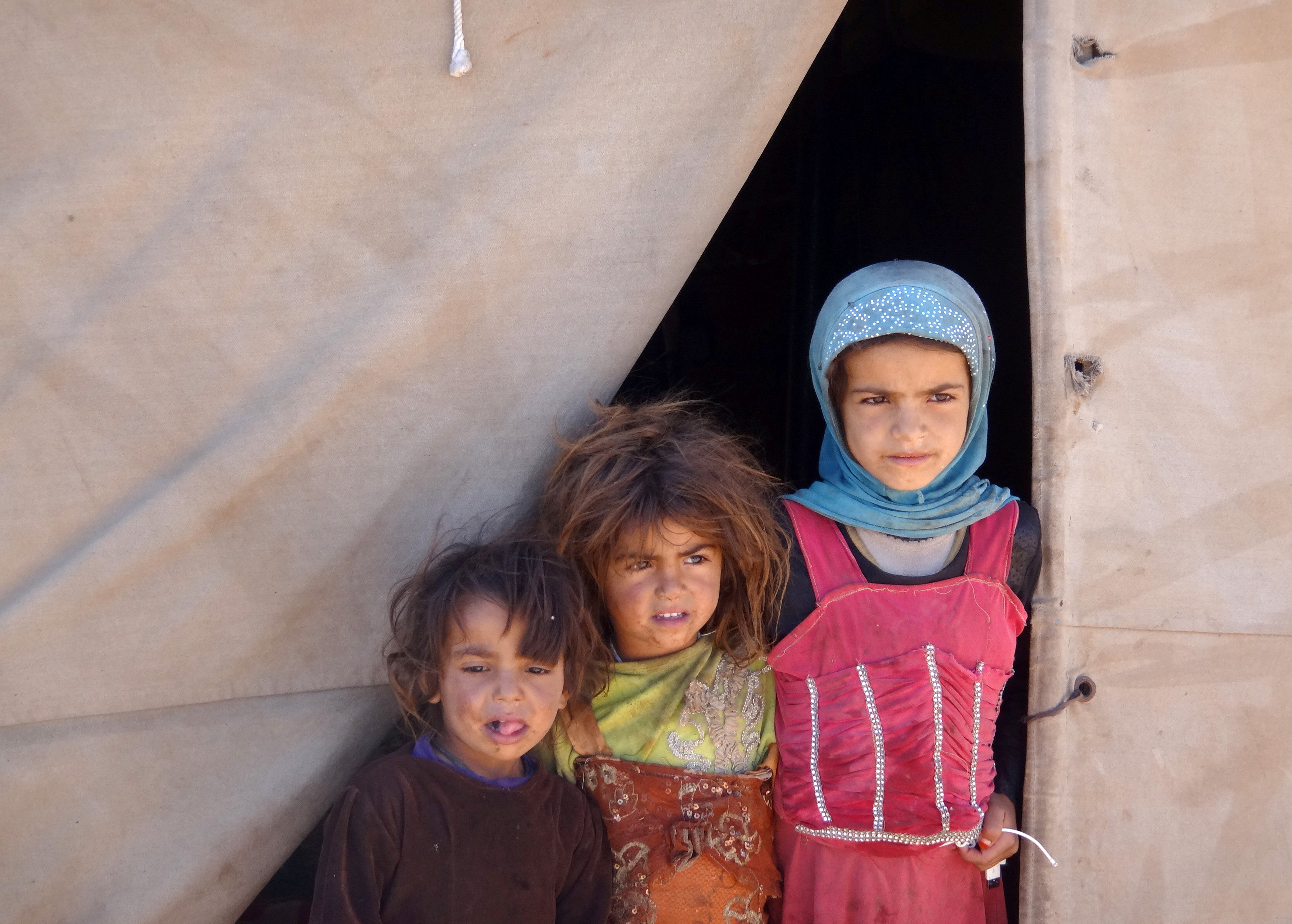 girls stand at the entrace of tent in yemen