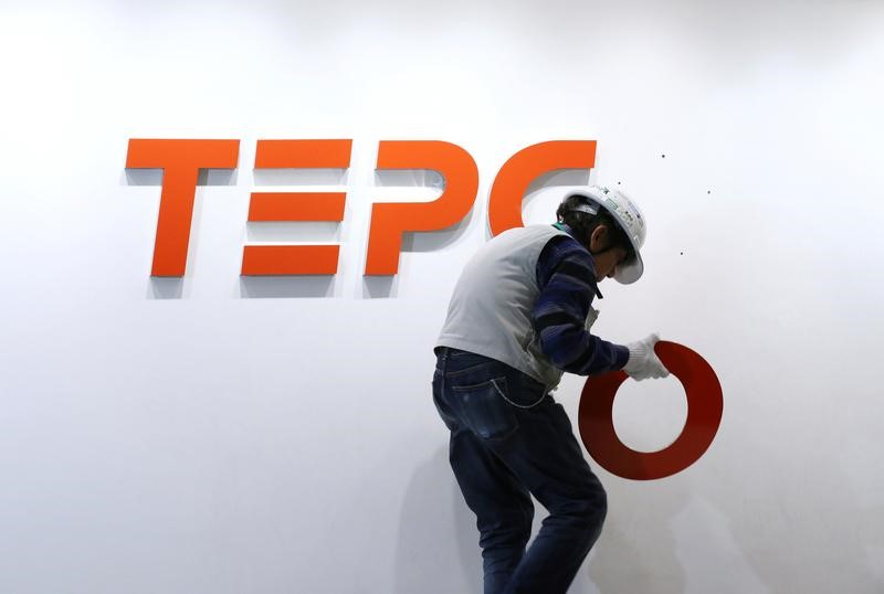 A worker puts up new logo of TEPCO Holdings and Tokyo Electric Power Company (TEPCO) Group on the wall ahead of the transition to a holding company system through a compan