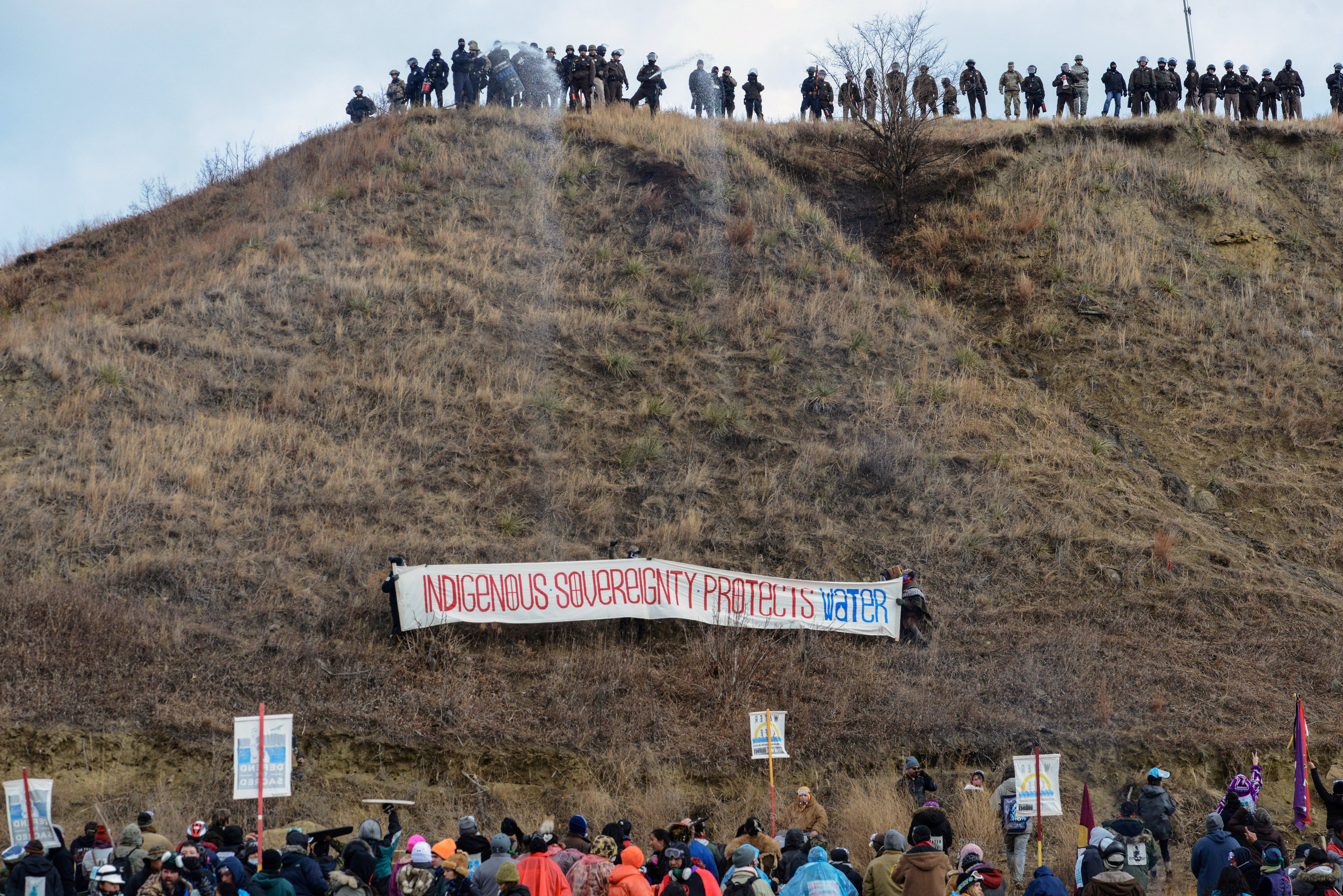 Protesters raise a banner regarding Dakota Access Pipeline