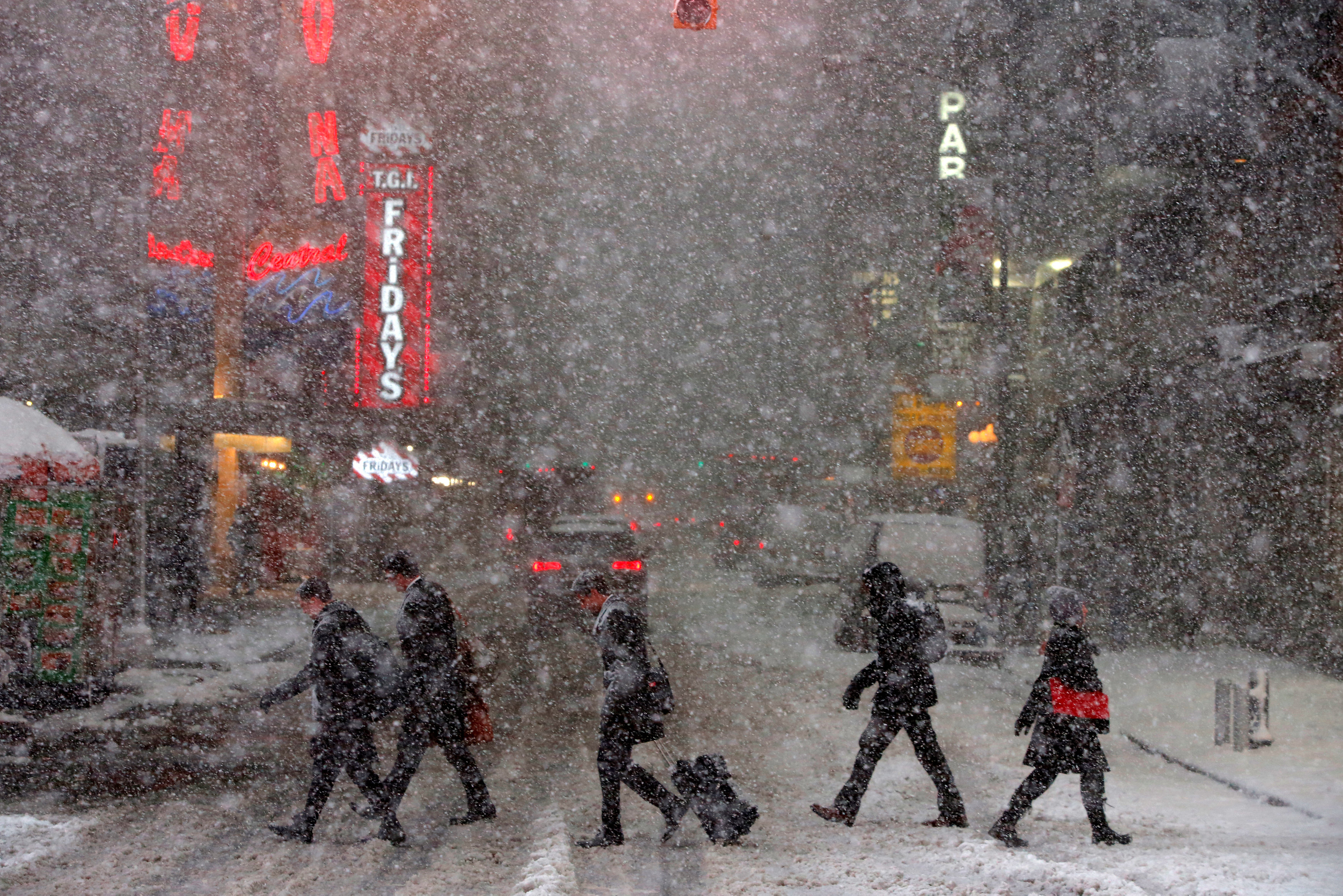 Pedestrians walk in Times Square as heavy snow falls
