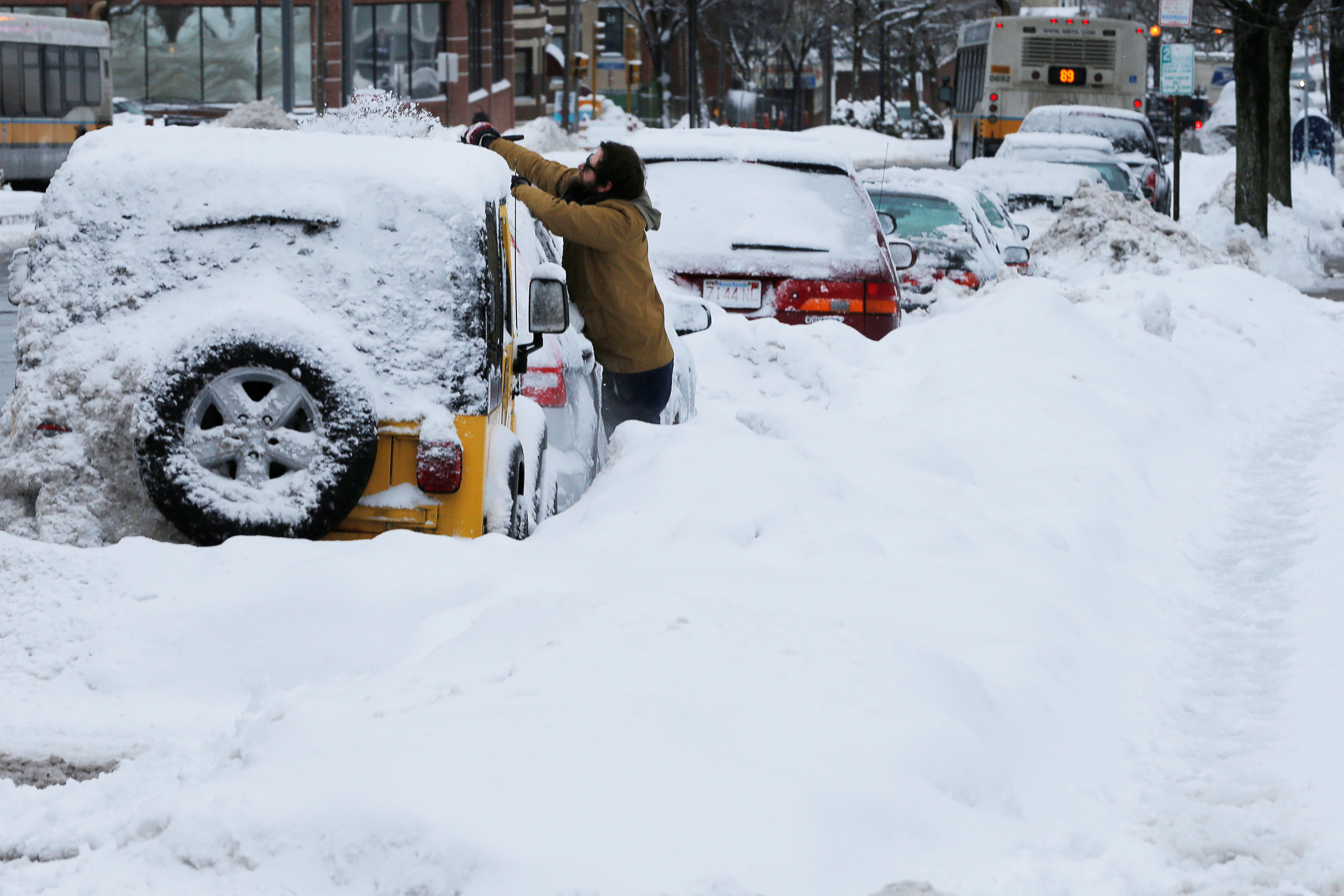 A man clears snow off his vehicle following a winter snow storm in Somerville,