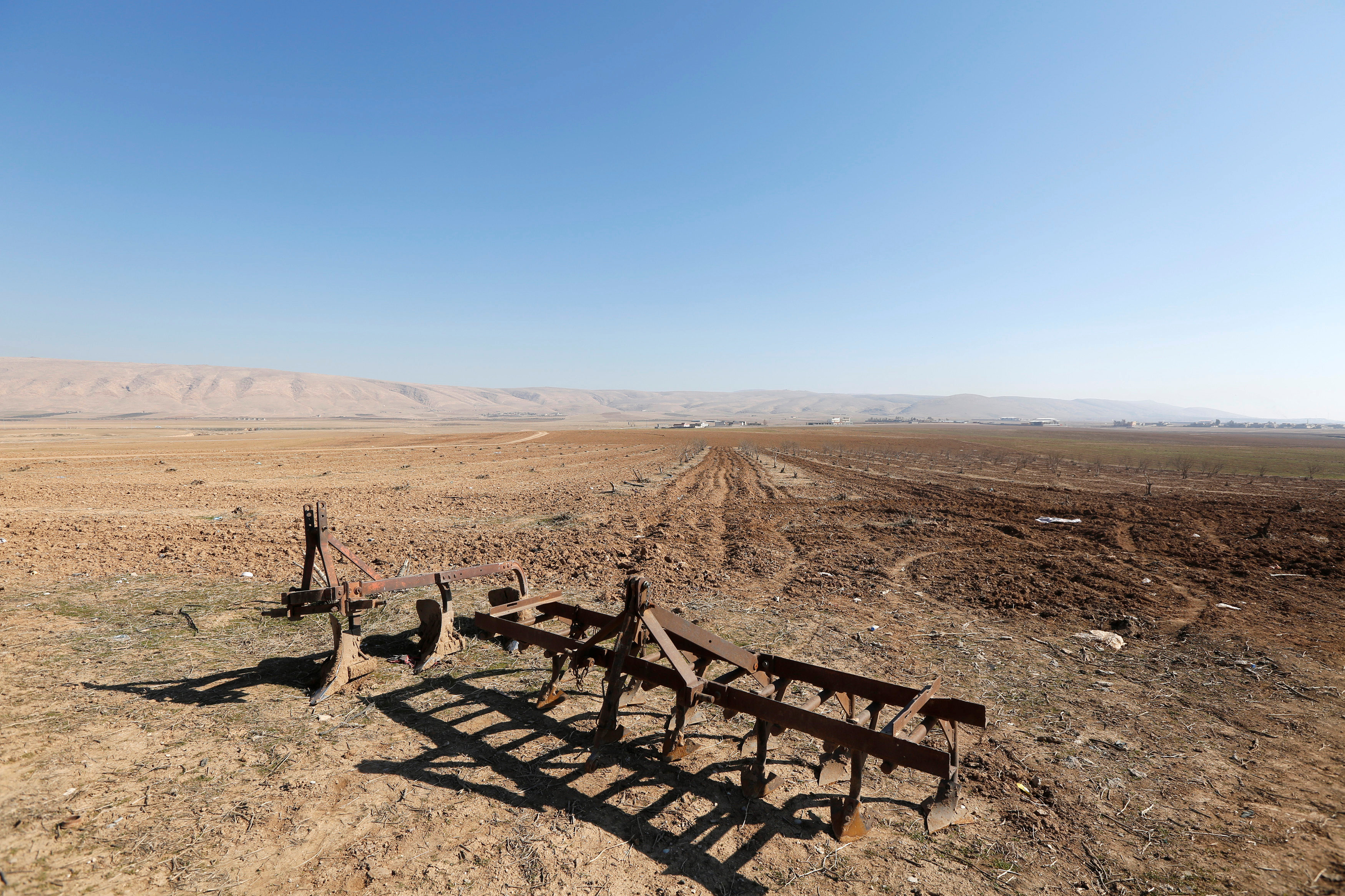 Parts of a bulldozer are seen at a farm in the town of Basheeqa, Iraq,