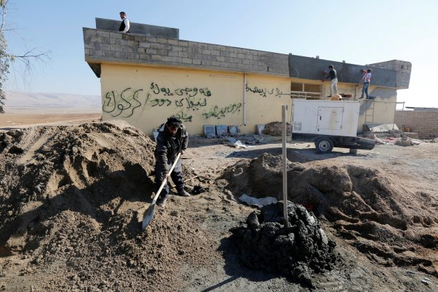 Workers repair a house after it was damaged during clashes in the town of Basheeqa, Iraq, February 8, 2017.