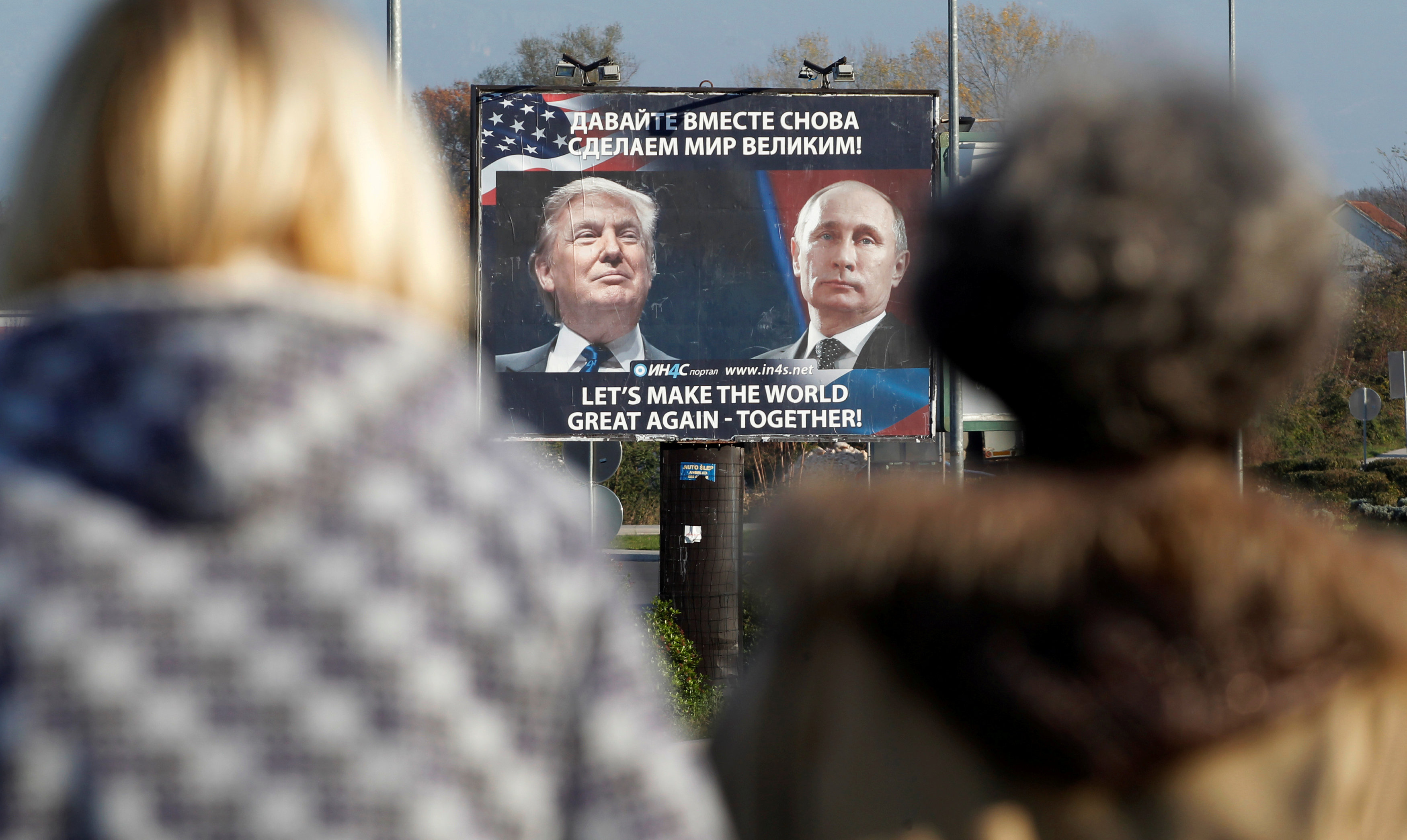 A billboard showing a pictures of US president-elect Donald Trump and Russian President Vladimir Putin is seen through pedestrians in Danilovgrad, Montenegro,