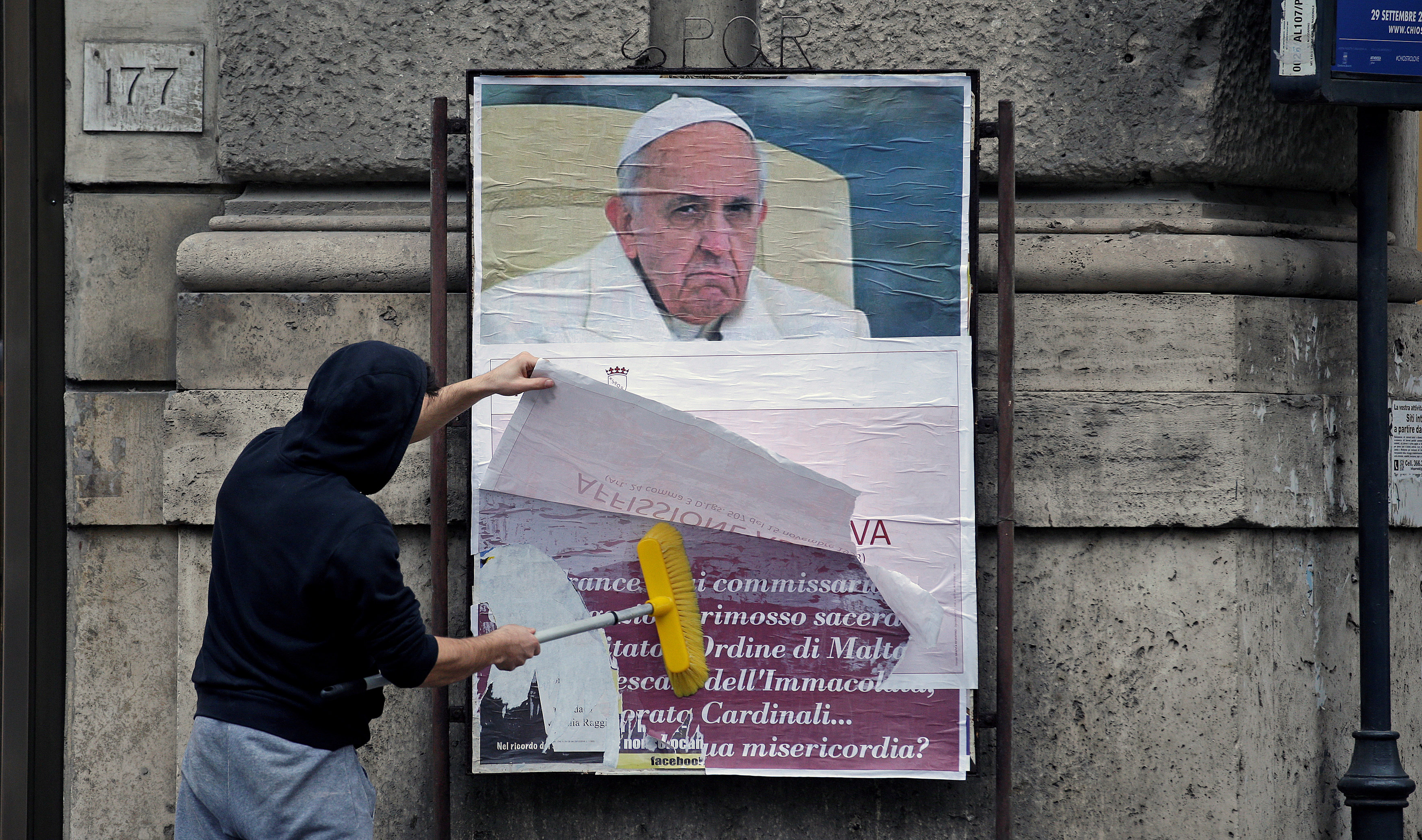 "A worker covers with a banner reading ""illegal poster"" a poster depicting Pope Francis and accusing him of attacking conservative Catholics, in Rome, Italy,"