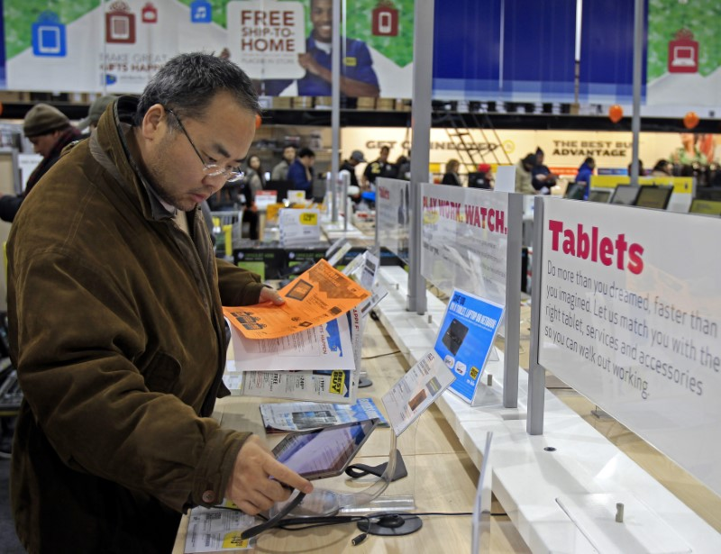 shopper looking at tablets in best buy
