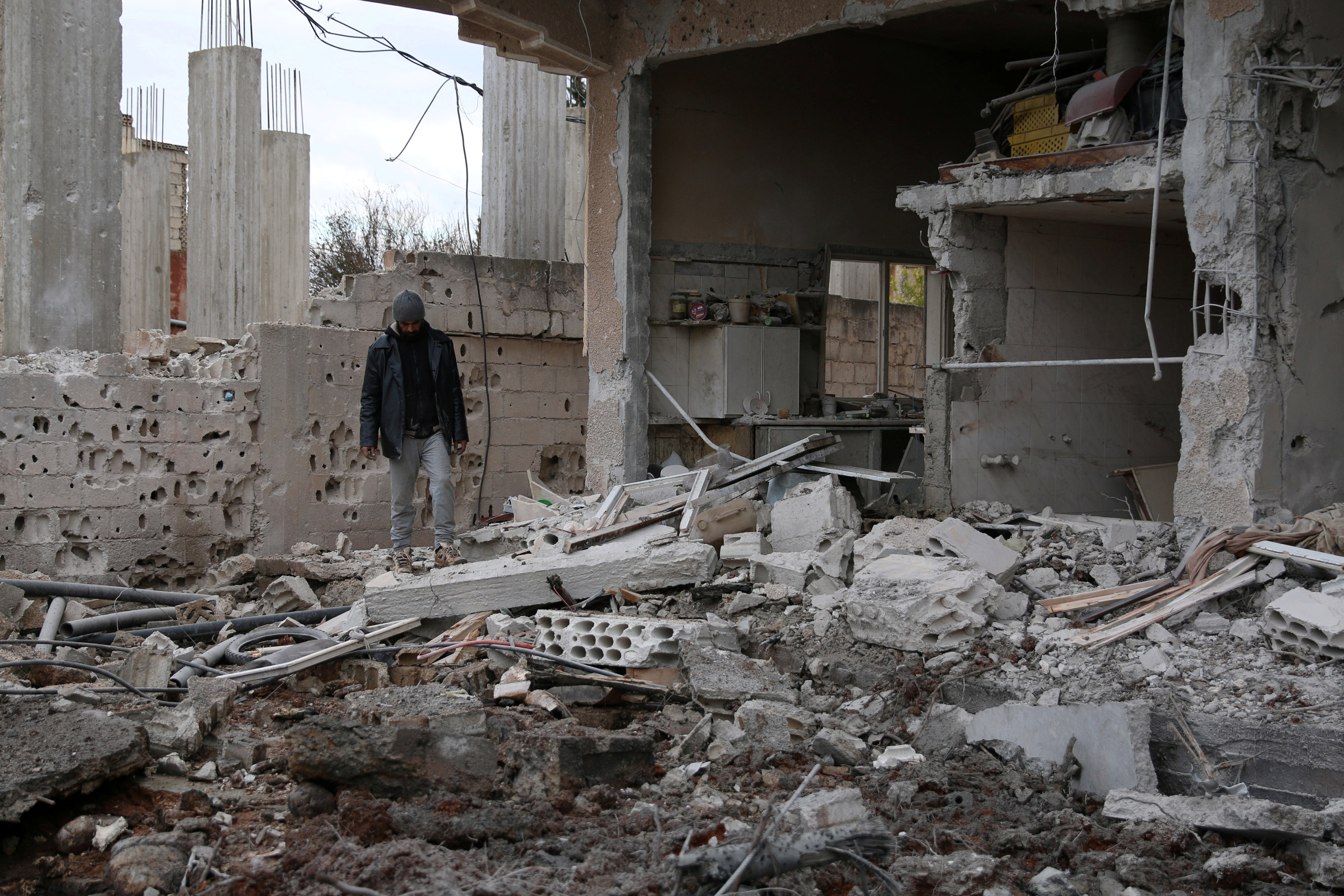 man inspects damaged house after airstrike in Syria