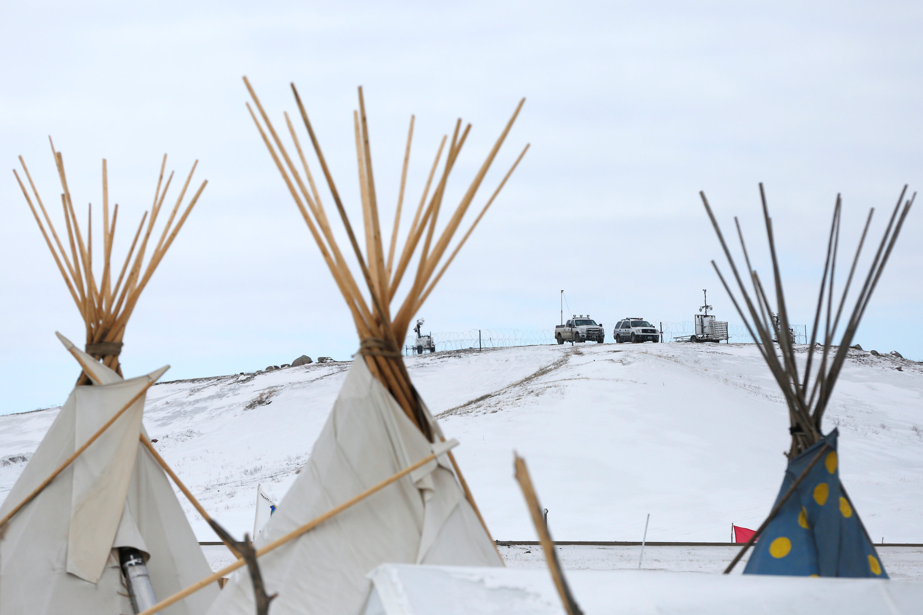 police vehicles sit on outskirts of protest camp in North Dakota