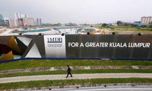 Man walks past Malaysia billboard at airport