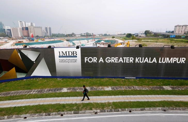 Man walks past Malaysia billboard at airport