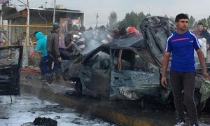 People and Iraq forces gather around car bombing sight