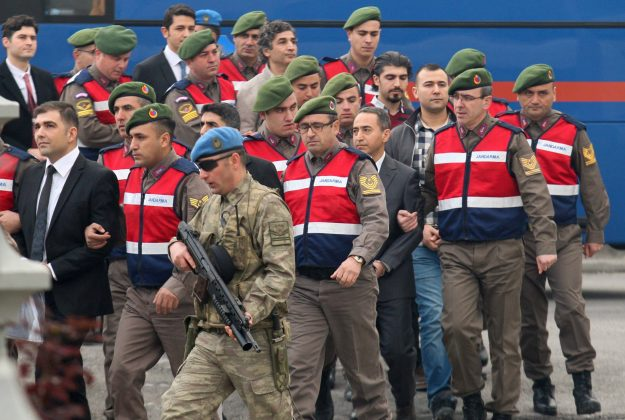 Turkish soldiers accused of attempting to assassinate President Tayyip Erdogan on the night of the failed last year's July 15 coup, are escorted by gendarmes as they arrive for the first hearing of the trial in Mugla, Turkey,