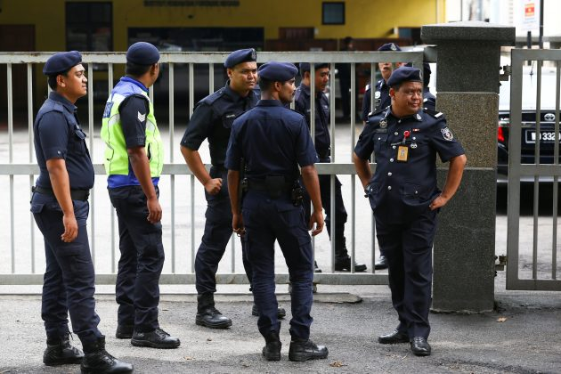 Malaysian police officers gather in front of the gate of the morgue at Kuala Lumpur General Hospital where Kim Jong Nam's body is held for autopsy in Malaysia February 21, 2017. REUTERS/Athit Perawongmetha